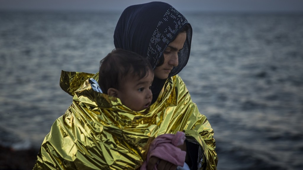 A woman wearing a thermal blanket holds her child on a beach on the Greek island of Lesbos shortly after crossing the Aegean sea on a dinghy from the Turkey's coast with other refugees and migrants on Friday, Nov. 20, 2015. Most nations along Europe's refugee corridor, except Greece, abruptly shut their borders Thursday to those not coming from war-torn countries such as Syria, Afghanistan or Iraq, leaving thousands desperately seeking a better life in the continent stranded at Balkan border crossings. (AP Photo/Santi Palacios)